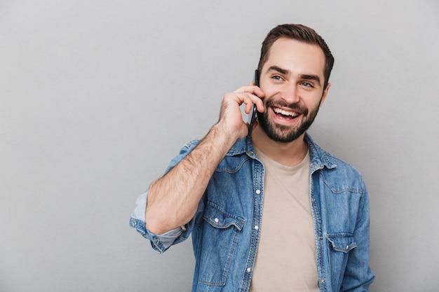 Eccitato uomo allegro che indossa camicia isolata sopra il muro grigio, parlando al telefono cellulare