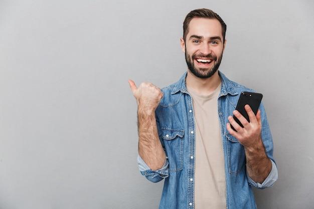 Eccitato uomo allegro che indossa una camicia isolata sopra il muro grigio, utilizzando il telefono cellulare, indicando lontano
