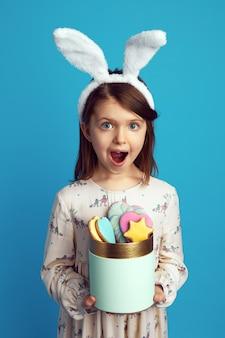 Bambino eccitato che tiene una scatola con biscotti con orecchie da coniglio e vestito carino