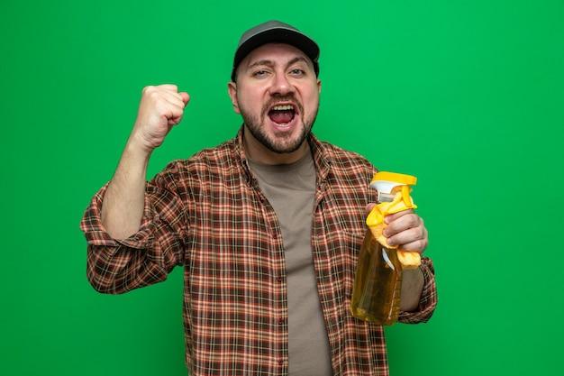 Uomo delle pulizie eccitato che tiene in mano panni per la pulizia e detergente spray che tiene il pugno