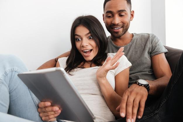Coppia eccitata che vince online guardando contenuti in un tablet seduto su un divano nel soggiorno di casa.