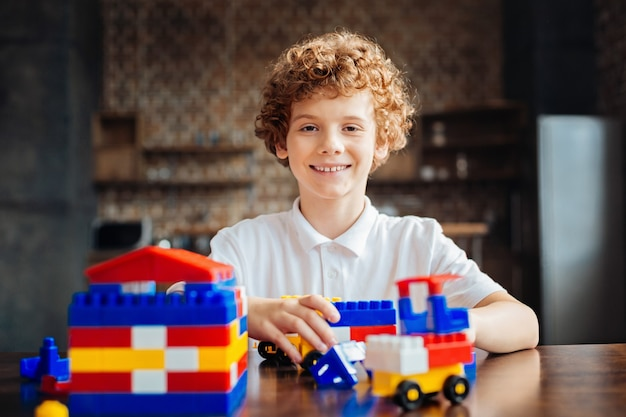 Eccitato ragazzo dai capelli ricci in posa per la fotocamera con un ampio sorriso sul viso mentre era seduto dritto a un tavolo e gioca con un set di costruzioni.