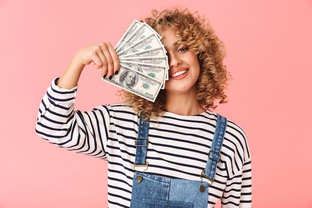 20s donna riccia eccitata che tiene fan di soldi del dollaro mentre levandosi in piedi