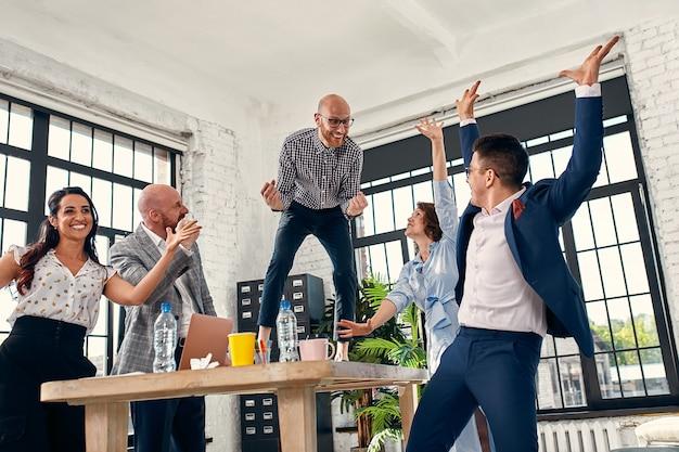 Dipendenti del team aziendale diversificato entusiasti che gridano per celebrare il successo aziendale di buone notizie