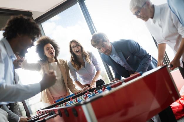 Diversi dipendenti emozionati che ridono godendosi attività divertenti durante la pausa di lavoro, lavoratori creativi e amichevoli giocano insieme