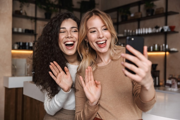 Eccitate ragazze emotive amiche sedute al bar prendono un selfie telefono cellulare salutando parlando