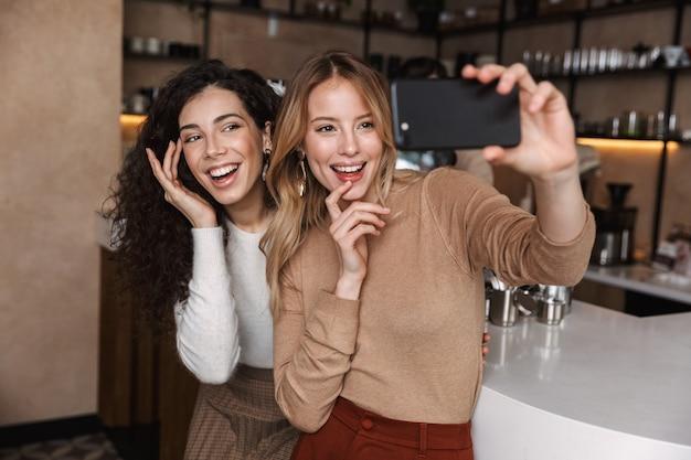 Eccitate ragazze emotive amiche sedute al bar si fanno un selfie con il cellulare
