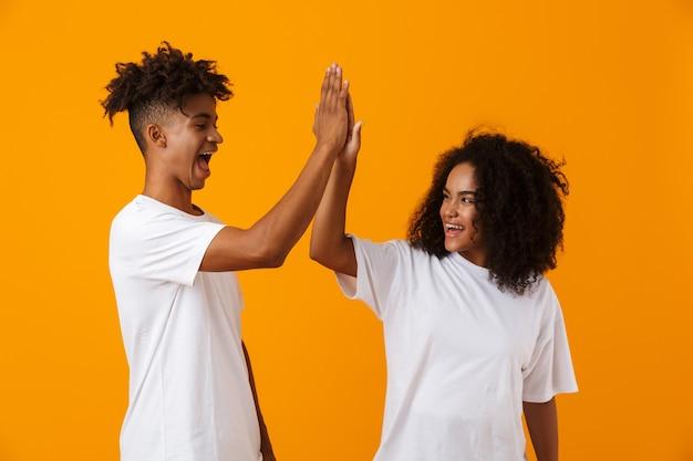 Emozionante giovane coppia africana carina emotiva in posa isolato sopra lo spazio giallo si dà il cinque a vicenda.