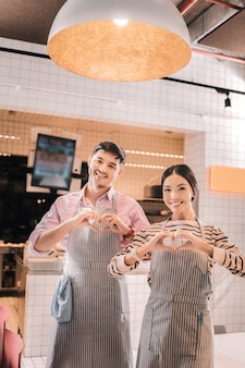 Imprenditori entusiasti. coppia di giovani imprenditori di bell'aspetto che si sentono eccitati all'apertura della loro sala caffè