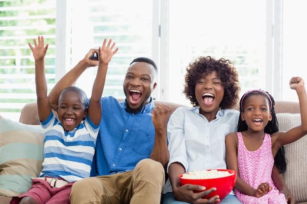 Famiglia emozionante e bambini che guardano la televisione mentre mangiano popcorn in salotto