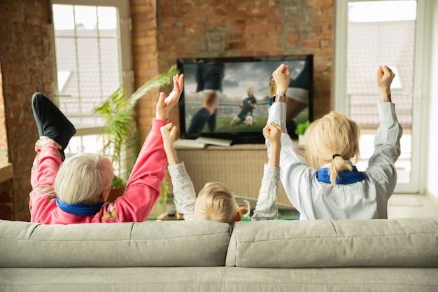 Famiglia eccitata che guarda il calcio, partita sportiva a casa. nonna, madre e figlio tifo per la squadra nazionale di calcio femminile con traduzione. divertirsi. concetto di emozioni, supporto, tifo.