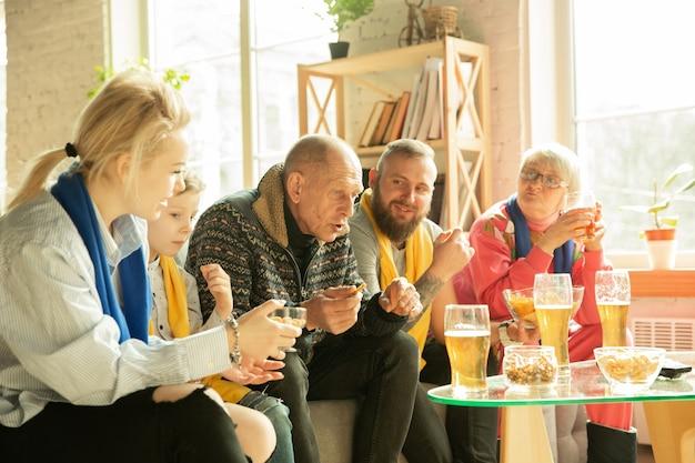 Famiglia eccitata che guarda il calcio, partita sportiva a casa. nonni, genitori e bambino tifo per la squadra nazionale di basket, calcio, tennis, calcio, hockey preferita. concetto di emozioni, supporto.