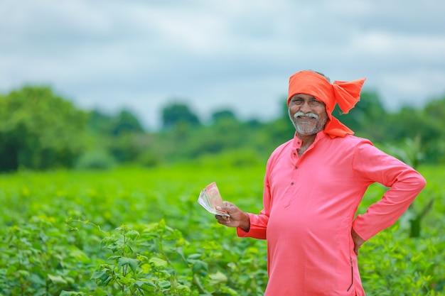 Coltivatore emozionante che tiene le note della rupia indiana