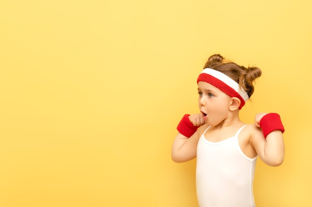 Bambino emozionante di forma fisica che posa nella fascia rossa sopra la parete gialla