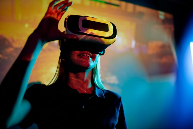 Ragazza eccitata in occhiali di realtà virtuale che testano il nuovo videogioco contro lo schermo di proiezione in camera oscura
