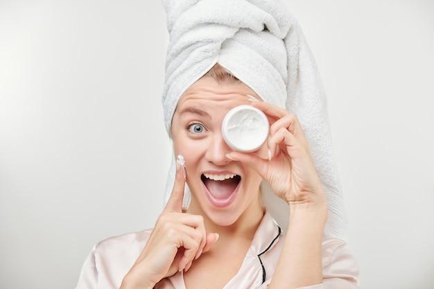 Ragazza emozionante con l'asciugamano sulla testa che tiene il barattolo di crema idratante per il viso dall'occhio sinistro mentre si applica il prodotto sulla guancia