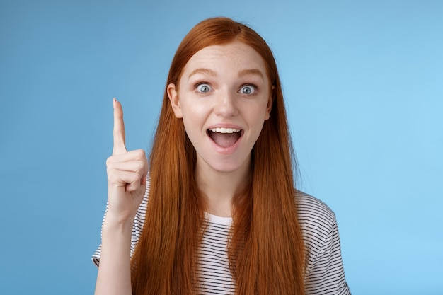 Eccitato goodlooking allegro zenzero fidanzata aggiungi idea conversazione alza il dito indice eureka gesto bocca spalancata raccontare suggerimento sorridere ampiamente meditando eccellente variante sfondo blu