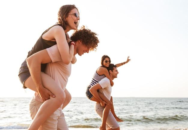 Gruppo emozionante di amici che amano le coppie che camminano all'aperto sulla spiaggia divertendosi