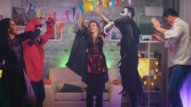 Eccitato gruppo di persone vestite per halloween in diversi personaggi che ballano e si divertono alla festa in casa.