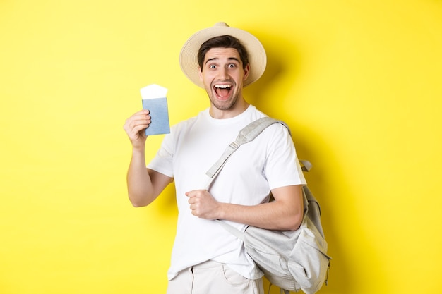 Turista di ragazzo eccitato che va in viaggio di vacanza, mostrando il passaporto con i biglietti e tenendo lo zaino, in piedi sopra il muro giallo