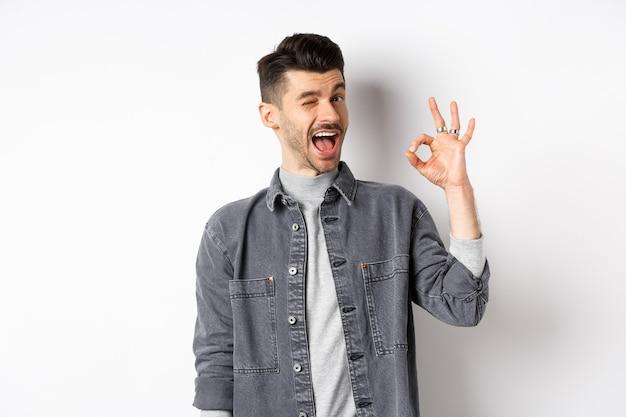 Eccitato bel ragazzo con i baffi, ammiccante e mostrando segno ok, sorridendo compiaciuto, assicura tutto bene, elogia il buon lavoro, fa un buon gesto di lavoro, in piedi su sfondo bianco.