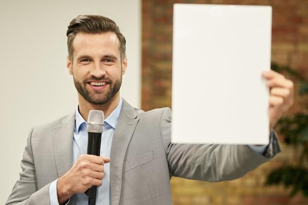 Eccitato bell'uomo con microfono che fa pubblicità a qualcosa