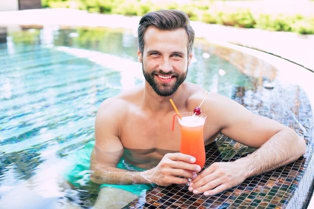 Uomo muscoloso moderno bello eccitato sta riposando nella piscina estiva e beve un cocktail rinfrescante e guarda sulla fotocamera.