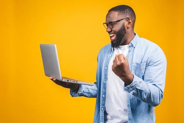Uomo afroamericano felice emozionante che esamina lo schermo del computer portatile e che celebra la vittoria