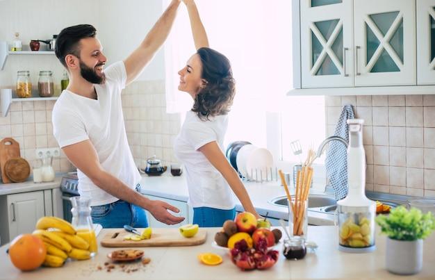 Bella giovane coppia felice emozionante nell'amore cucinare in cucina e divertirsi insieme ballando e sorridendo
