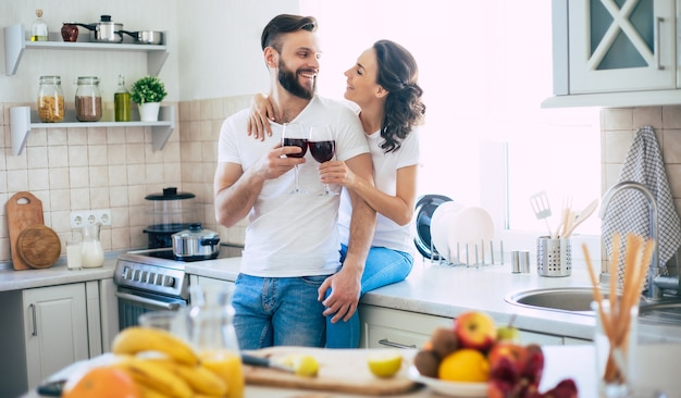 Bella giovane coppia felice emozionante nell'amore cucinare in cucina e divertirsi insieme mentre si prepara insalata di frutta fresca e sana