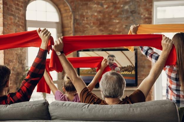 Una grande squadra familiare eccitata e felice guarda la partita sportiva insieme sul divano di casa