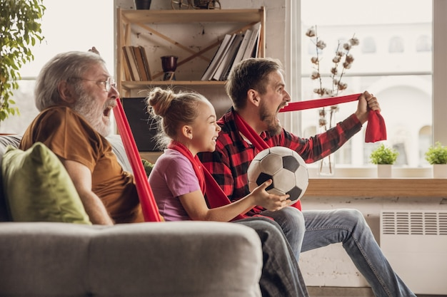 Grande famiglia eccitata e felice che guarda il calcio, la partita di calcio sul divano di casa. tifo emozionato dei tifosi per la squadra nazionale preferita. divertirsi da nonno a figlia. sport, tv, campionato.