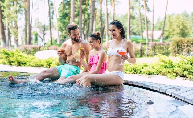 La bella giovane famiglia moderna felice eccitata in piscina estiva durante una vacanza in hotel si diverte e beve dei cocktail.