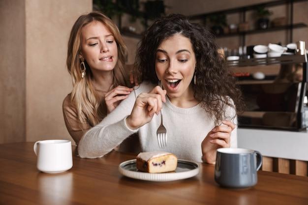 Eccitati felici belle ragazze amiche sedute al bar a bere caffè mangiano torta