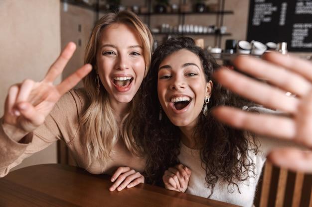 Eccitati e felici belle ragazze amiche sedute al bar si fanno un selfie con la macchina fotografica
