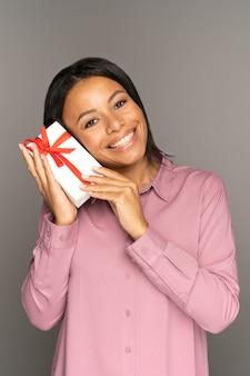Eccitata donna felice tiene un regalo in una scatola avvolta decorata ricevi un regalo per il compleanno di natale o il nuovo anno