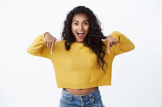 Eccitato felice giovane donna afro-americana carina in maglione giallo ansimando stupito rivolto verso il basso, promuovere una bella pubblicità, guardare la macchina fotografica, suggerire un'offerta incredibile sul muro bianco