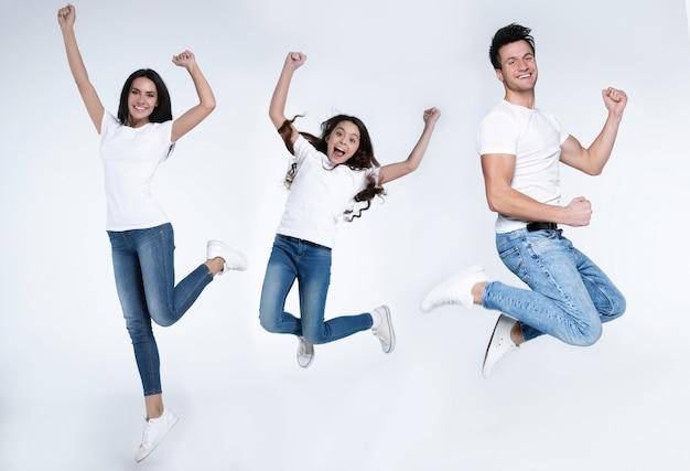 La giovane bella famiglia emozionante e felice sta saltando e gridando in magliette bianche e jeans isolati su fondo bianco.