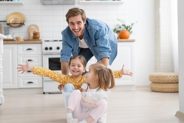 Eccitato e felice giovane padre corre a spingere una scatola di cartone con bambine carine che cavalcano dentro, divertendosi.