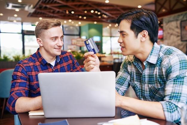 Giovani felici eccitati che discutono della carta di credito hanno ricevuto in banca per iniziare una nuova attività