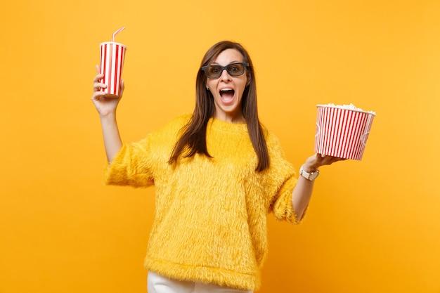 Eccitato giovane donna felice in occhiali 3d imax guardando film, tenendo secchio di popcorn e tazza di plastica di cola o soda isolato su sfondo giallo. persone sincere emozioni nel cinema, nello stile di vita.