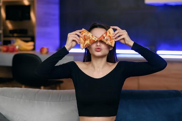Giovane donna felice emozionante nella cucina che plaing con le fette della pizza. copri gli occhi con il cibo. governante spensierata molto giocosa. indossa una vestaglia bianca. casalinga incurante.