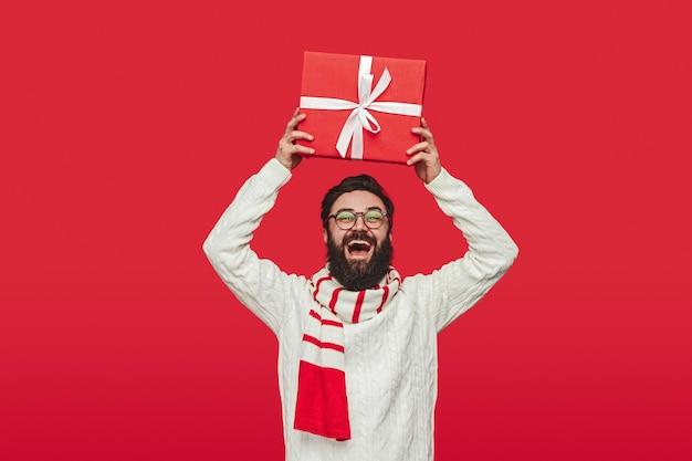 Eccitato hipster scuotendo regalo di natale sopra la testa