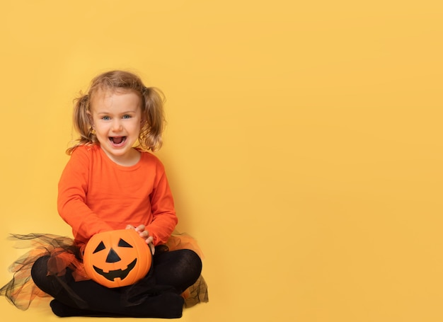 Eccitato bambino zucca halloween strega costume posa isolato giallo studio sfondo tenere caramelle bucket