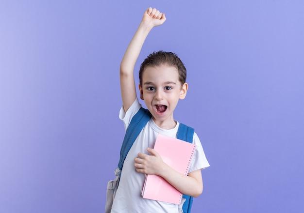 Eccitato ragazzino che indossa uno zaino guardando la fotocamera che tiene il blocco note facendo sì gesto isolato sulla parete viola con spazio copia
