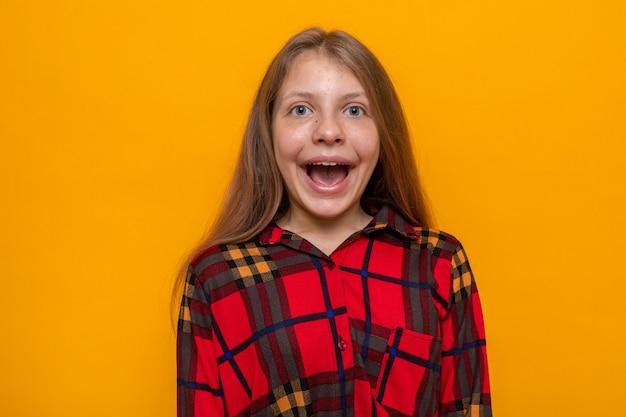 Bella bambina dall'aspetto eccitato che indossa una maglietta rossa