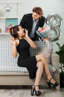 Eccitato guardarsi l'un l'altro giovane coppia durante la felice giornata delle donne ragazzo con bouquet in piedi dietro al divano con una ragazza nel soggiorno