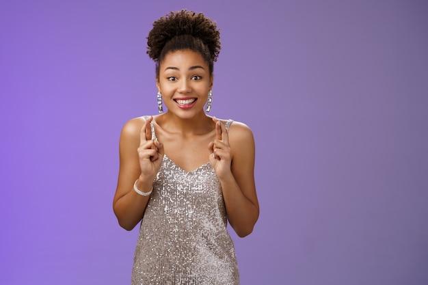 Eccitato fortunato speranzoso affascinante modello femminile afroamericano spera di vincere la concorrenza dita incrociate sognante sorridente ottimista credere fortuna pregando sogno che si avvera, esprimi il desiderio sfondo blu.