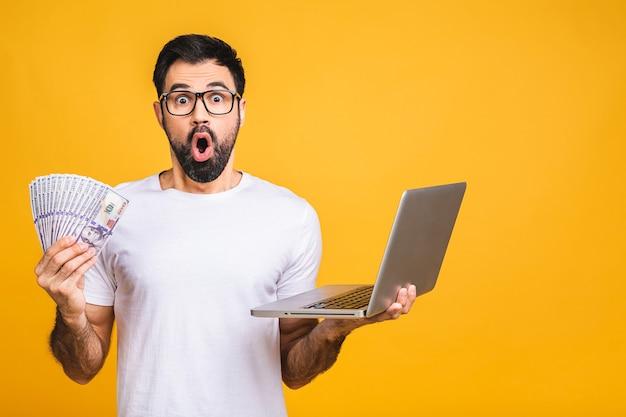 Uomo eccitato in casual tenendo un sacco di soldi in valute del dollaro e laptop in mani isolate su sfondo giallo.
