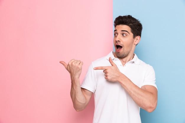 Uomo eccitato in maglietta casual sorridente e mostrando a copyspace sul palmo della mano, isolato su un muro colorato